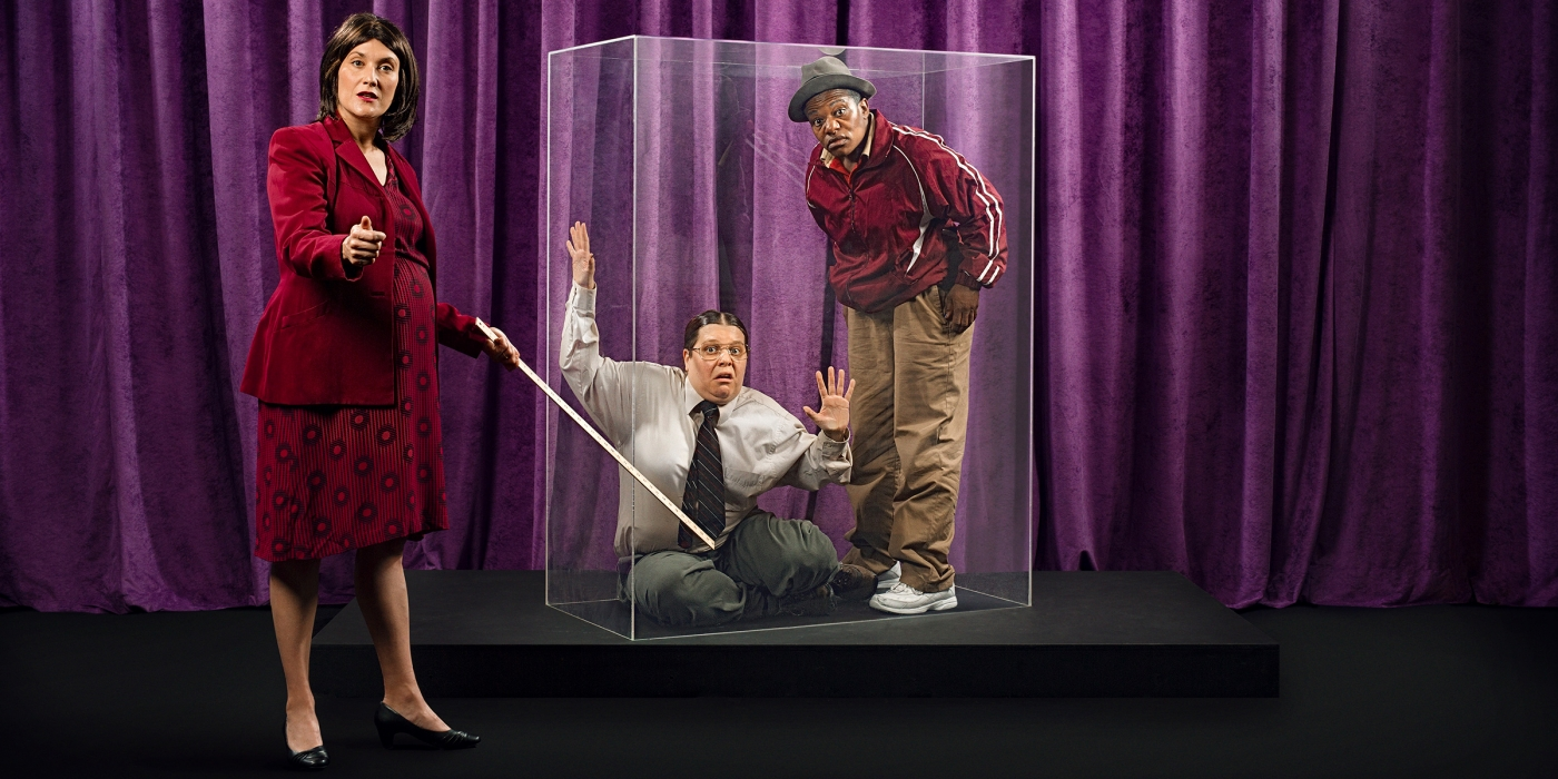 A pregnant professor points at two plexiglass-imprisoned pals.