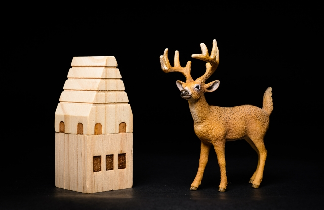 A photograph of a toy deer and a wooden toy house.